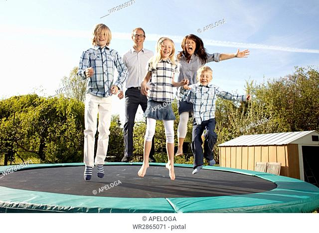 Happy family jumping on trampoline in back yard against sky