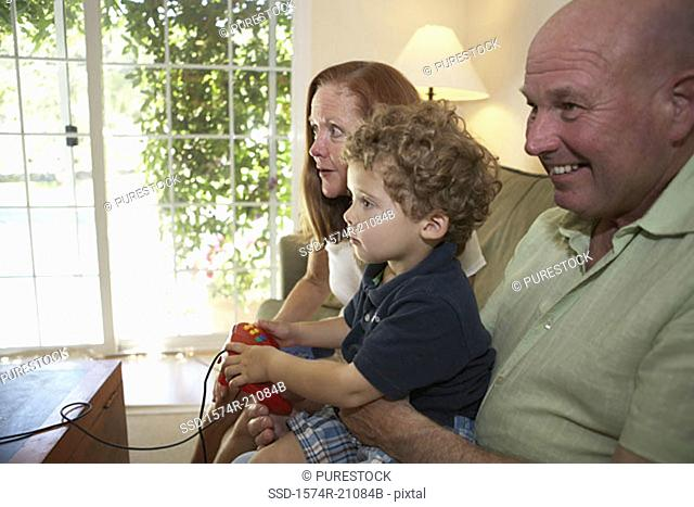 Side profile of a boy sitting with his grandparents and playing a video game
