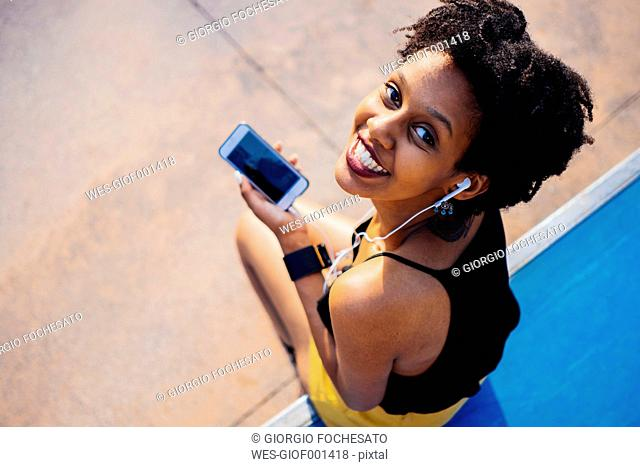 Smiling young woman with earphones and cell phone sitting in a skatepark looking up to camera