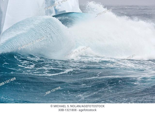 Massive waves breaking on iceberg detail in and around the Antarctic Peninsula during the summer months  More icebergs are being created as global warming is...