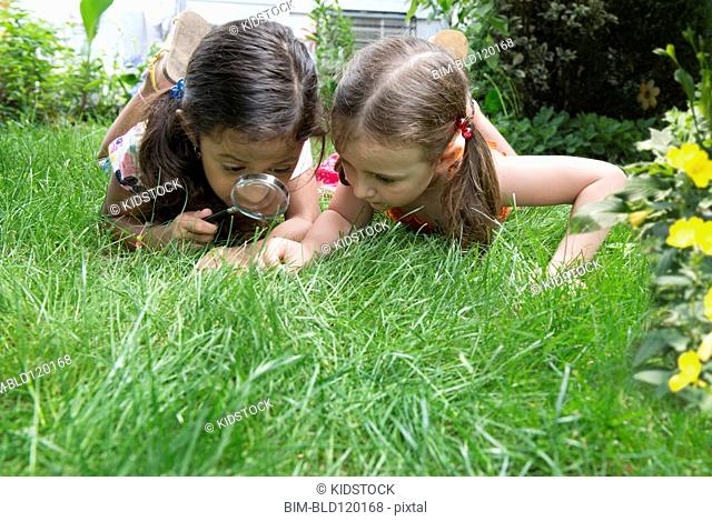 Girls using magnifying glass in grass