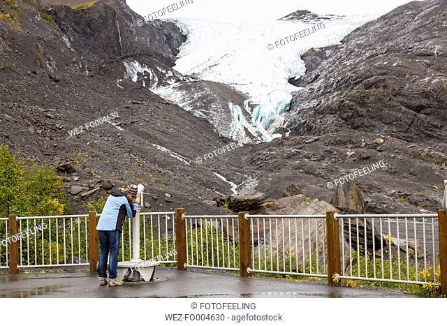 USA, Alaska, Tourist looking through binocular at Worthington Glacier