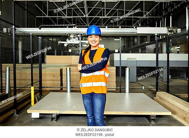 Portrait of smiling female worker in factory warehouse