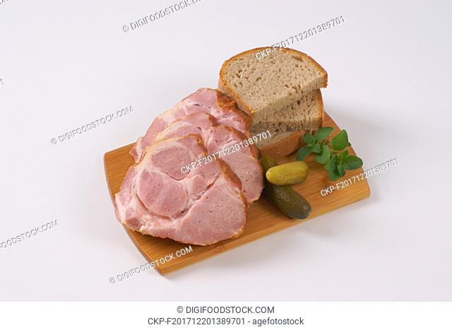 slices of smoked pork neck with bread on wooden cutting board