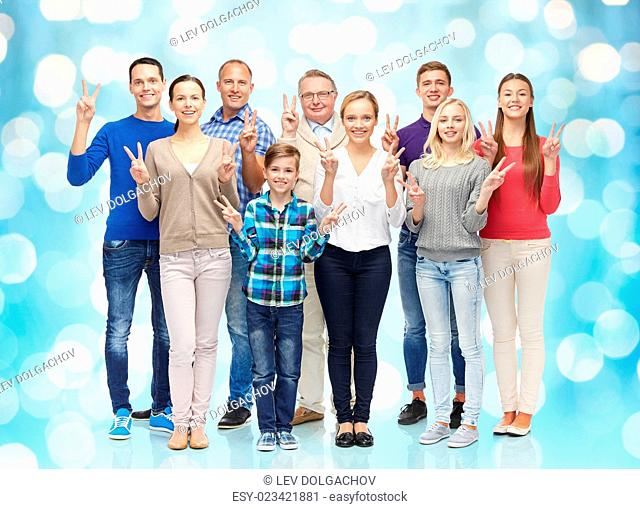 family, gender, victory and people concept - group of smiling men, women and boy showing peace hand sign over blue holidays lights background