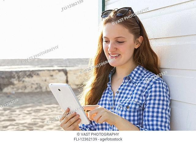 Girl using tablet at Woodbine beach in summer; Toronto, Ontario, Canada