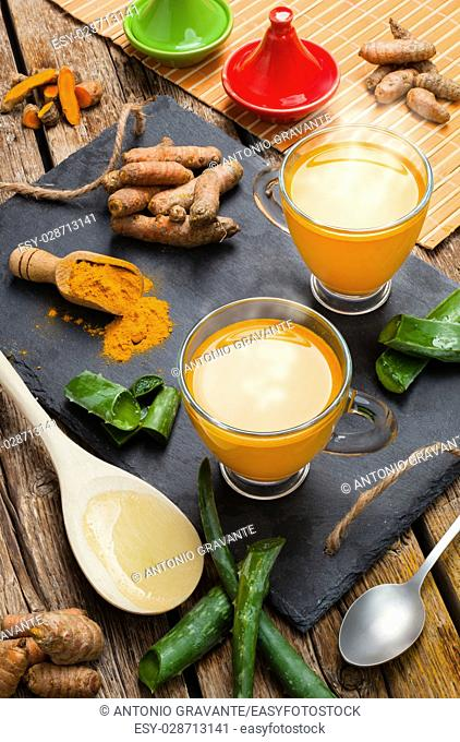 Hot drink with aloe vera and turmeric. Glass cups on a slate tray
