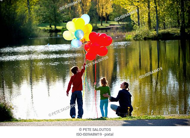 Mother and children in front of lake with bunches of balloons