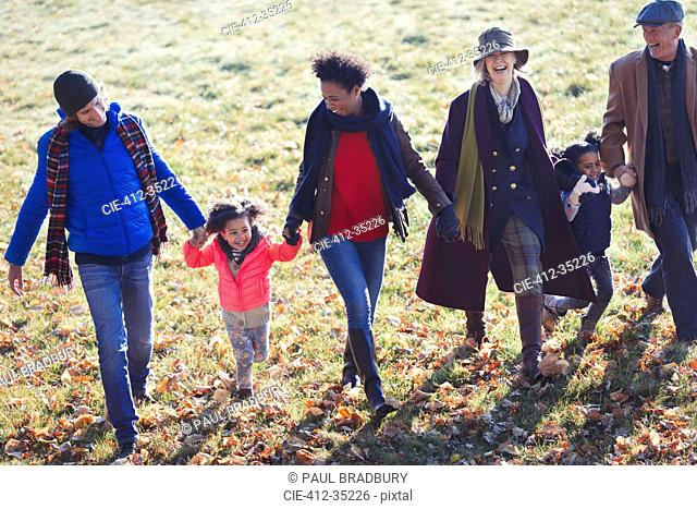Multi-generation family holding hands and walking in sunny autumn park