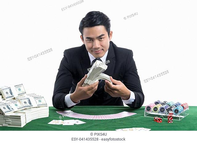 A Handsome man is smiling and holding piles of banknotes in hands, dollars placed nearby, has gambling devices , spread cards, the bets on green table