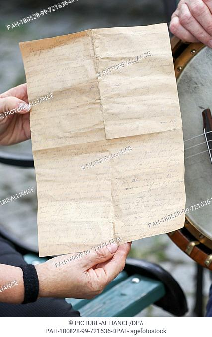 20 August 2018, Germany, Markneukirchen: A hobby instrument collector presents an old love letter from a banjo written in pencil