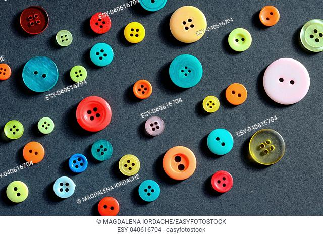 Isolated clothing colorful buttons on black background