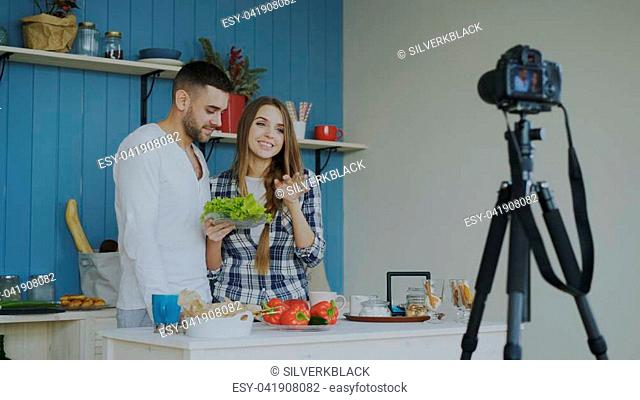 Young attractive couple recording video blog about vegetarian healthy food on dslr camera in the kitchen at home