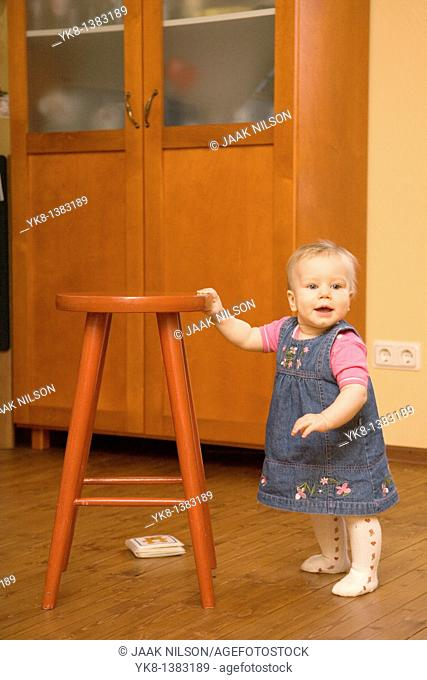 Happy Eight Month Old Infant Girl Standing by Stool Chair