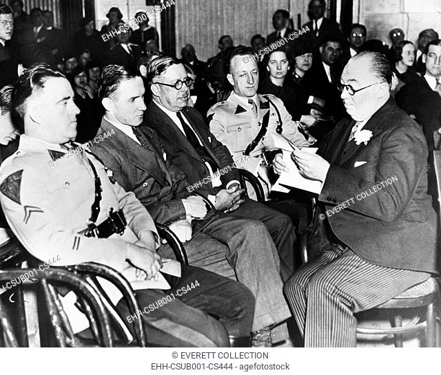 Bruno Hauptmann (2nd from felt) sitting between State Troopers and a Sheriff at his trial. At right holding paper is Hauptmann's defense counsel, Edward J