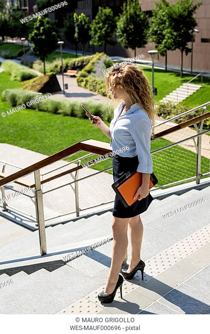 Businesswoman holding cell phone, book and digital tablet outdoors