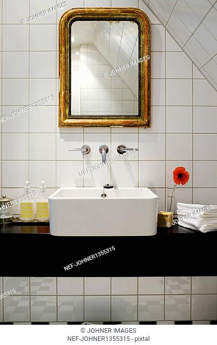 Antique mirror and modern sink in bathroom