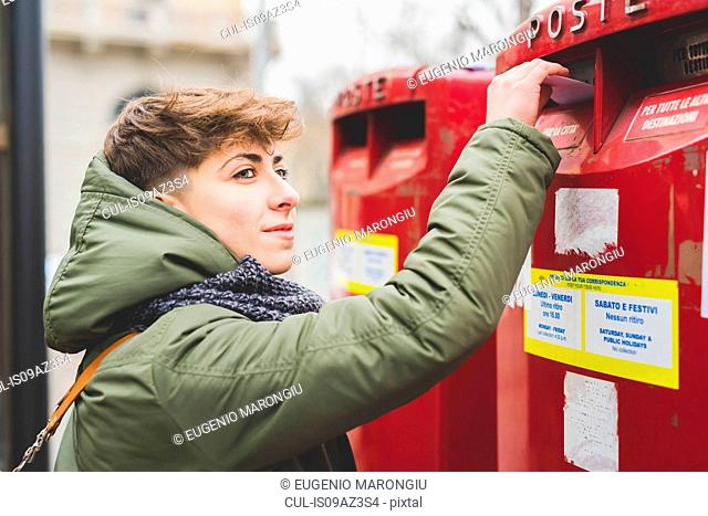 Young woman posting letter