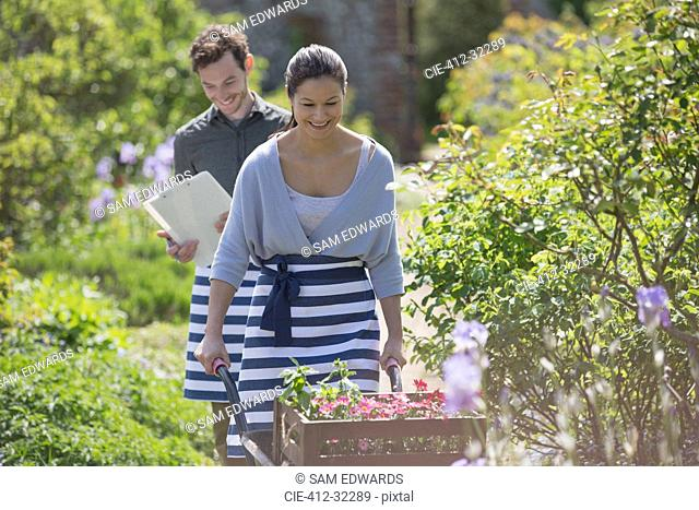 Smiling plant nursery worker pushing wheelbarrow with flowers in sunny garden