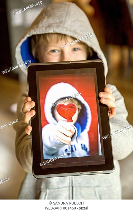 Boy showing digital tablet with photography of himself