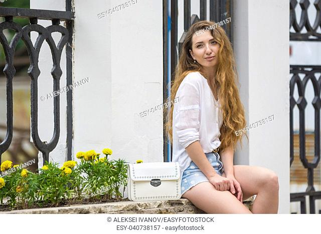 A young girl with a lady's white handbag crouched in the alley on the street