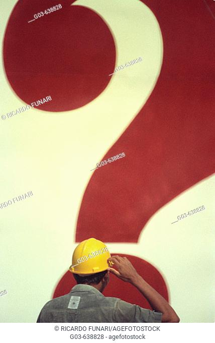 Construction worker in front of a question mark