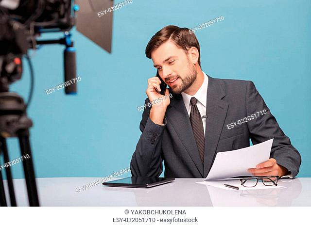 Cheerful young tv newscaster is talking on the mobile phone and smiling. He is sitting at desk in studio in front of the camera