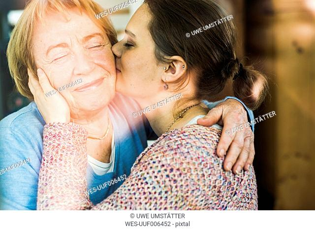 Young woman kissing senior woman behind windowpane