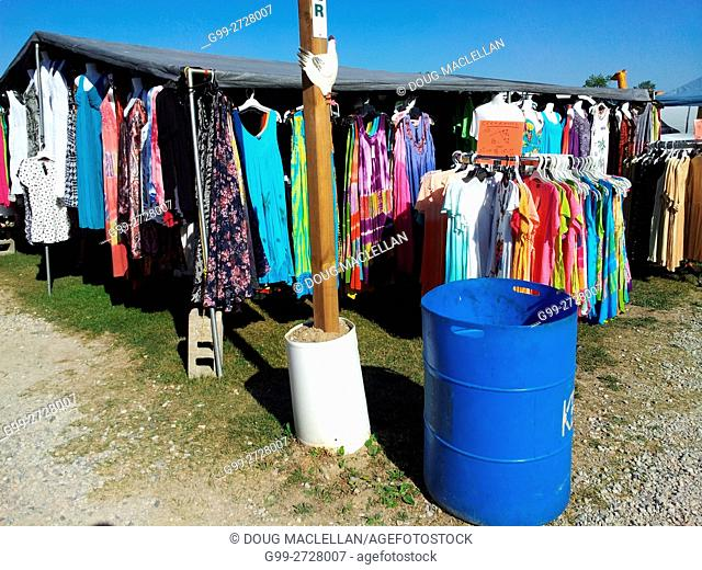 A blue barrel, signpost and hanging clothes in a vendor's booth at an intersection of paths at a weekly flea market in rural Ontario, Canada