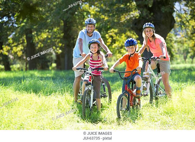 Family, mountain biking, in treelined field