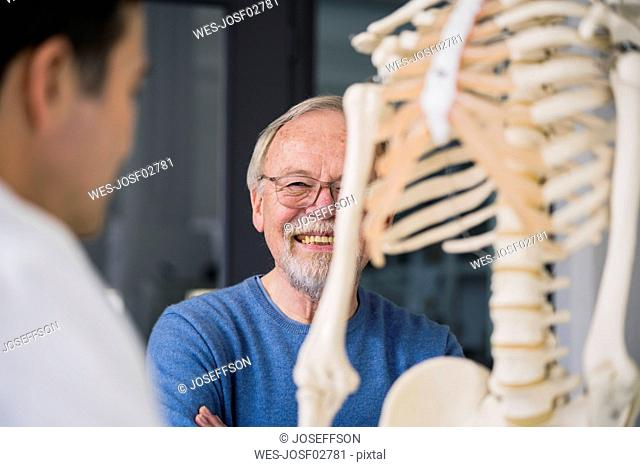Smiling senior patient with doctor in medical practice with anatomic model