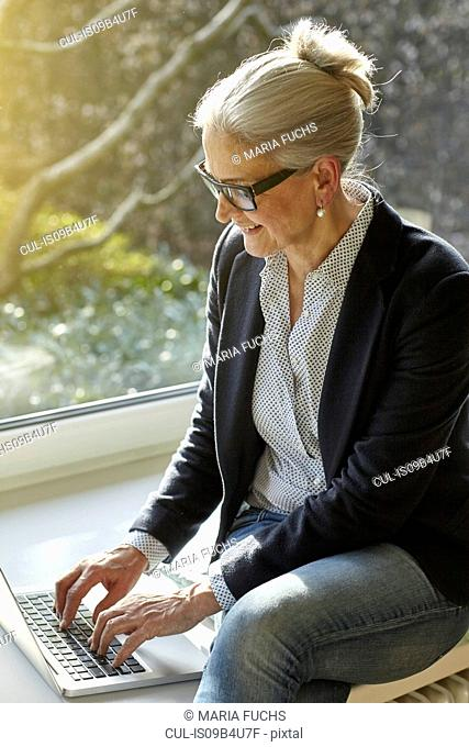 Senior businesswoman typing on laptop at home on windowsill