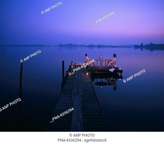 Couple enjoying summer evening at a lake