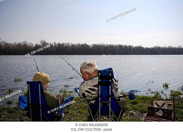 Grandfather and grandson 12-14 fishing by river, rear view