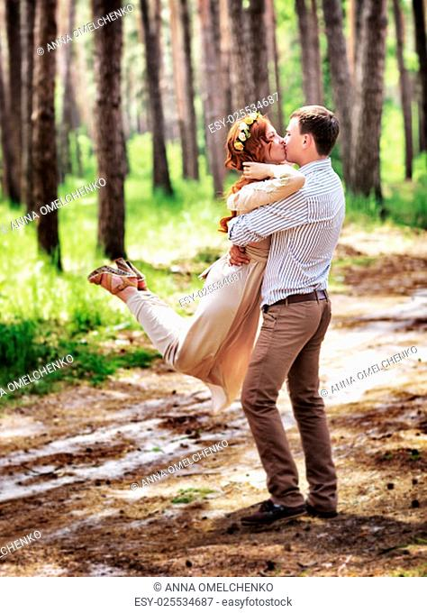 Happy couple in the forest, having fun outdoors in wedding day, groom lifted and whirls his lovely bride, enjoying romantic relationship