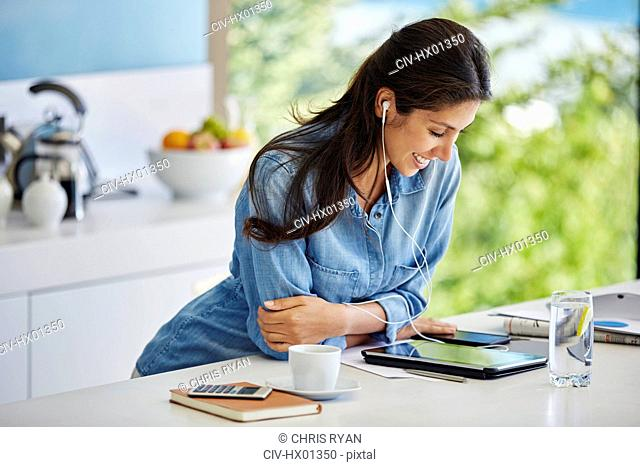 Smiling woman listening to music with headphones and mp3 player in kitchen