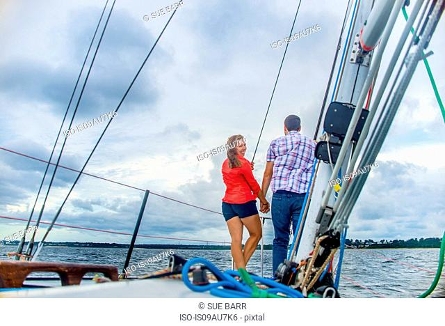 Rear view of couple on bow of boat holding hands, looking over shoulder at camera smiling
