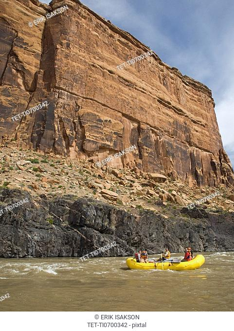 People in raft under cliff