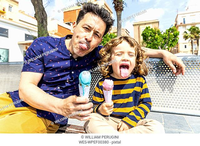 Spain, Barcelona, happy father and son sitting on bench enjoying an ice cream
