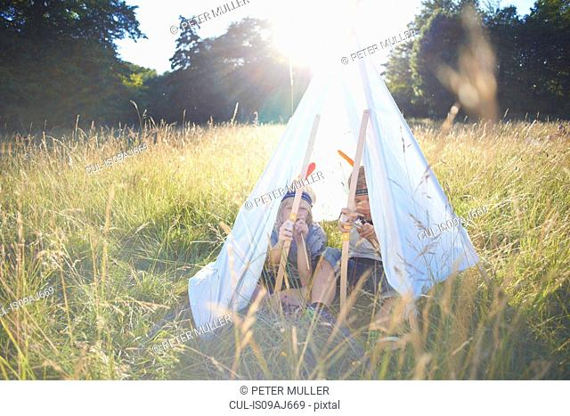 Two young boys sitting inside a teepee