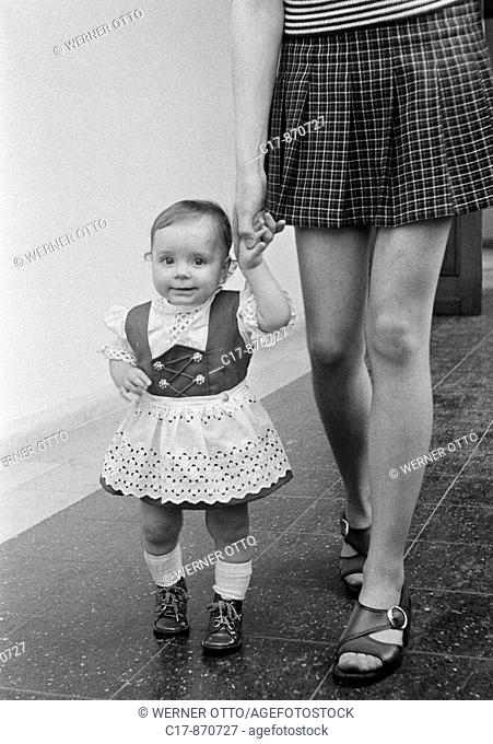 Seventies, black and white photo, people, young mother takes a walk with her little daughter, aged 20 to 25 years, aged 2 to 3 years