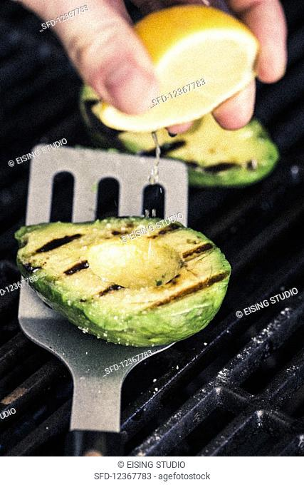 Grilled avocado being drizzled with lemon juice