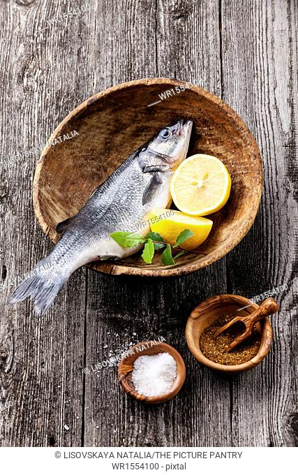 Fresh raw fish seabass with salt, spices and lemon on textured wooden background