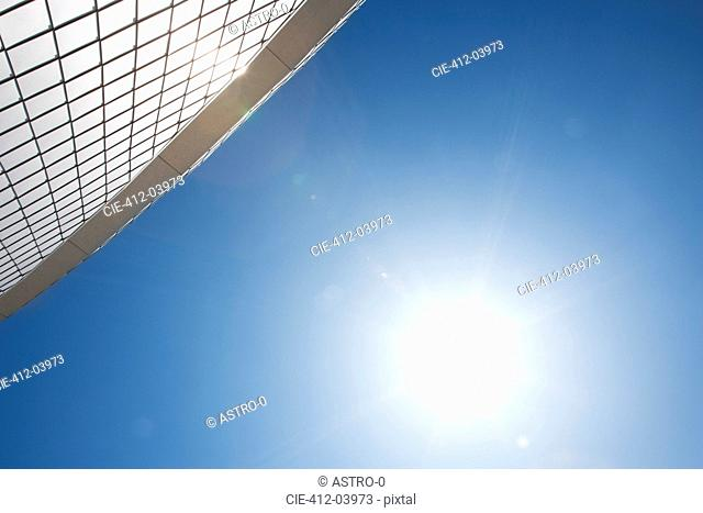 Sun by modern building in blue sky