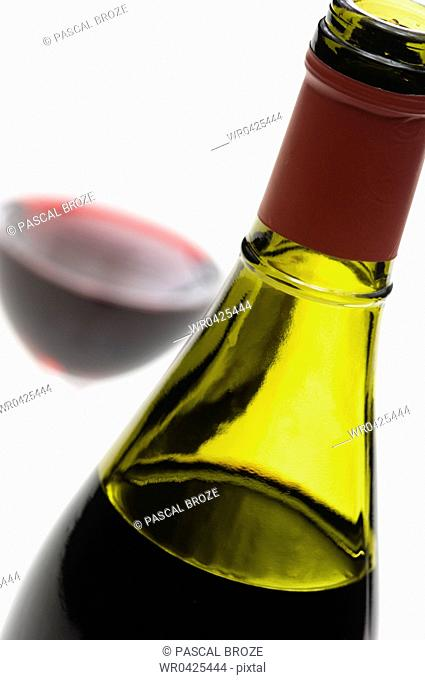 Close-up of a wine bottle with a glass of red wine in the background