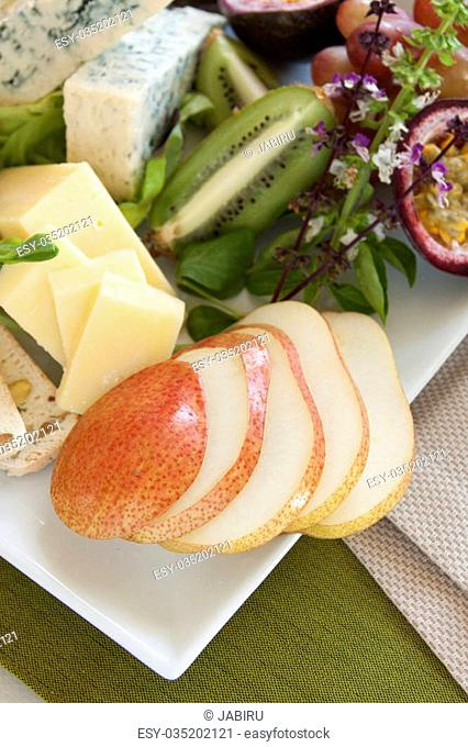 Delicious fruit and cheese platter featuring sliced pear and a variety of different cheeses and fresh fruits