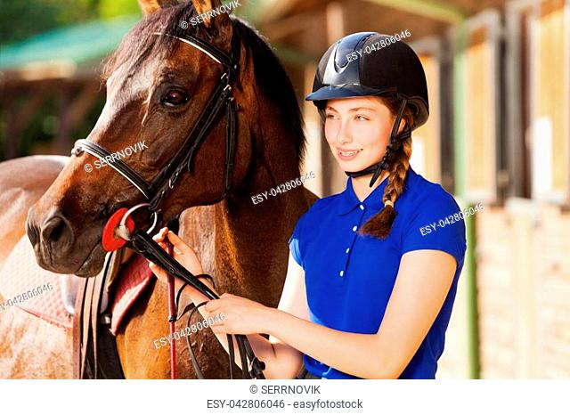 Portrait of beautiful jockey girl holding reins of her purebred bay horse standing next to the training stable at sunny day