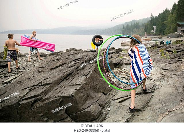 Family with pool rafts plastic hoops rocks lakeside