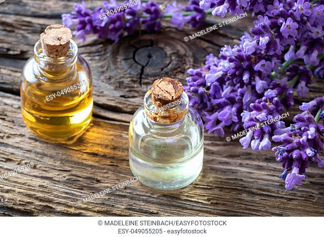 Bottles of essential oil with fresh blooming lavender twigs