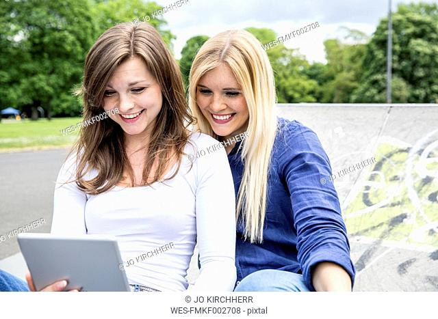Two smiling friends looking at tablet